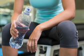 Fit woman sitting on bench holding water bottle — Stock Photo