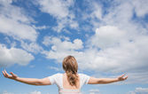 Woman with arms outstretched against blue sky and clouds — ストック写真