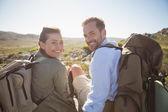 Hiking couple sitting on mountain terrain smiling at camera — Stock Photo
