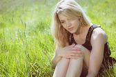 Pretty blonde in sundress sitting on grass — Foto de Stock