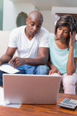Worried couple calculating bills on the couch — Stockfoto