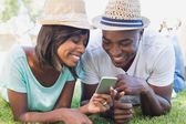 Happy couple lying in garden together looking at smartphone — Stockfoto