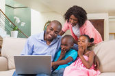Happy family relaxing on the couch using laptop — Stock Photo