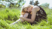 Pretty blonde in sundress sitting on grass — Stok fotoğraf