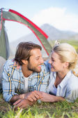 Couple lying in their tent about to kiss — Стоковое фото