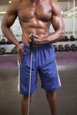 Muscular man using resistance band in gym — Stockfoto