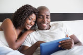 Happy couple cuddling in bed with tablet pc — Stock Photo