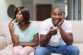 Woman sitting next to her boyfriend watching tv — Foto Stock