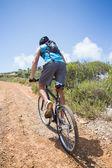 Man cycling up mountain trail — Stock Photo