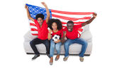 American football fans in red on the sofa — Stock Photo