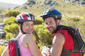 Fit cyclist couple sitting at the summit smiling at camera — Stock Photo