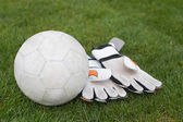 Goalkeeping gloves and football on pitch — Stockfoto