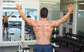 Bodybuilder with arms outstretched in gym — 图库照片