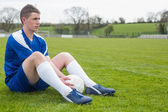 Football player in blue taking a break on the pitch — Stock Photo