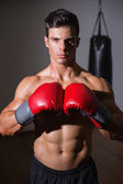 Shirtless muscular boxer in defensive stance — Stockfoto