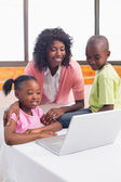 Cute siblings using laptop together with mother — Stock Photo