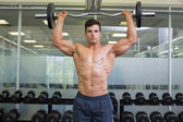 Shirtless muscular man lifting barbell in gym — Stock Photo