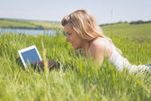 Pretty blonde lying on grass using her tablet — Foto Stock