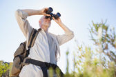 Hiker standing on country trail looking through binoculars — Stock Photo