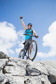 Man cycling on rocky terrain and cheering — Stock Photo
