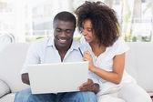 ラップトップを使用して一緒にソファの上オンライン ショップを魅力的なカップル — ストック写真