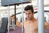 Muscular man exercising on a lat machine in gym — Stock Photo