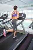 Fit brunette running on the treadmill — Stock Photo