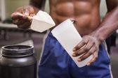Constructor del cuerpo sosteniendo una cuchara de la mezcla de proteínas — Foto de Stock