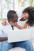 Attractive couple using laptop together on sofa  — Stock Photo