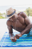 Handsome shirtless man listening to music poolside — Stock Photo
