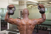 Muscular man lifting kettle bells in gym — ストック写真