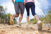 Couple running up mountain trail — Stock Photo