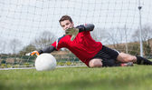 Goalkeeper in red saving a goal during a game — Stock Photo