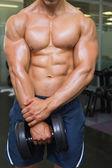 上半身裸の筋肉男がダンベルで運動の中間部分 — ストック写真