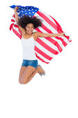 Pretty girl wrapped in american flag jumping — Stockfoto