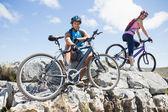Cyclist couple taking break on rocky peak — Foto de Stock