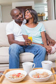 Happy couple relaxing on the couch with juice — Stockfoto