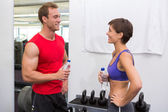 Fit attractive couple chatting holding water bottles — Stock Photo