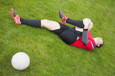 Football player in red lying injured on the pitch — Stock Photo