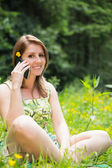 Relaxed woman using mobile phone in field — Stock Photo