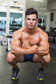 Shirtless muscular man flexing muscles in gym — Stock Photo