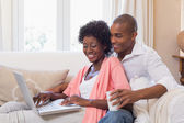 Cute couple relaxing on couch with laptop and coffee — Stock Photo