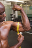 Muscular man measuring biceps in gym — Foto de Stock
