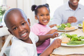 Family enjoying a healthy meal together with son smiling at came — Foto de Stock