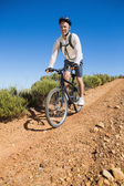 Fit cyclist cycling on country terrain — Stock Photo