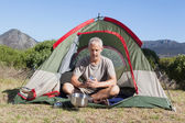 Happy camper holding mug outside his tent — Stock Photo