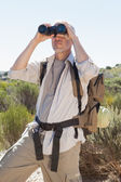 Hiker looking through binoculars on country trail — Stock Photo