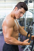 Shirtless muscular man using triceps pull down in gym — Стоковое фото
