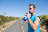 Athletic man on open road taking a drink — Foto de Stock