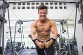 Shirtless muscular man using resistance band in gym — Stock Photo